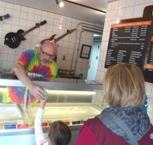 Gary jensen handing a dish of ice cream to a customer, Moosie's Ice Cream Parlor, Medford, WI.